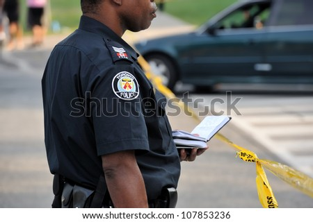 TORONTO-JULY 17: Toronto policeman taking notes at the crime scene where shooting leaves 2 dead and 21 injured on July 17, 2012 in Toronto