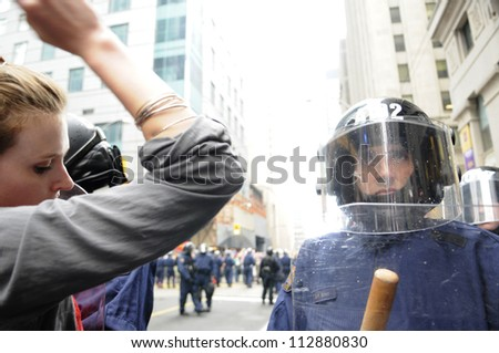 TORONTO-JUNE 26:  A female protester dancing in front of a riot police  during the G20 Protest on June 26, 2010 in Toronto, Canada.