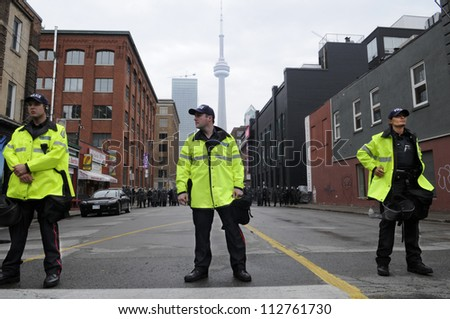 TORONTO-JUNE 26:   A group of Toronto police officers standing in front of a perimeter formed by the riot police during the G20 Protest on June 26 2010 in Toronto, Canada.