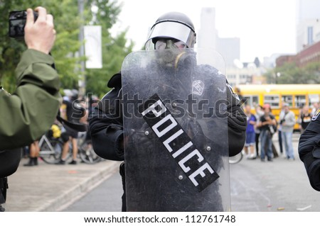 TORONTO-JUNE 26:   A man takes picture of a police in riot gear during the G20 Protest on June 26 2010 in Toronto, Canada.