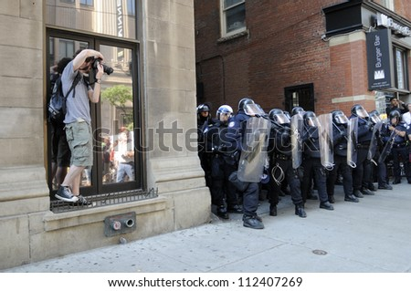 TORONTO-JUNE 25: A  photojournalist taking pictures of the riot police during the G20 Protest on June 25, 2010 in Toronto, Canada.