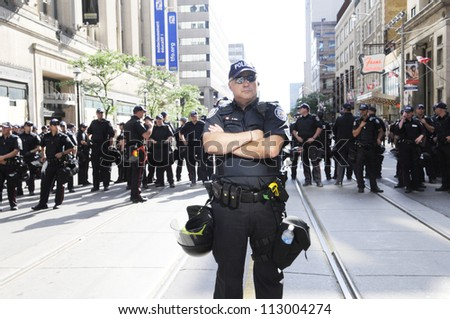 TORONTO-JUNE 28:  A police officer keeping a close and careful eye on the people on the streets  during the G20 Protest on June 28, 2010 in Toronto, Canada.