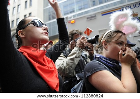 TORONTO-JUNE 26:  A protester chanting slogans while another one talking on her cell phone   during the G20 Protest on June 26, 2010 in Toronto, Canada. - stock photo