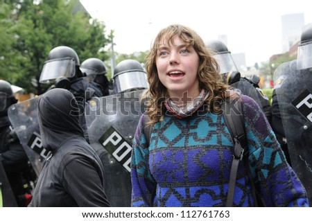 TORONTO-JUNE 26:  A  protester chanting slogans while being surrounded  by the riot police officers during the G20 Protest on June 26 2010 in Toronto, Canada.