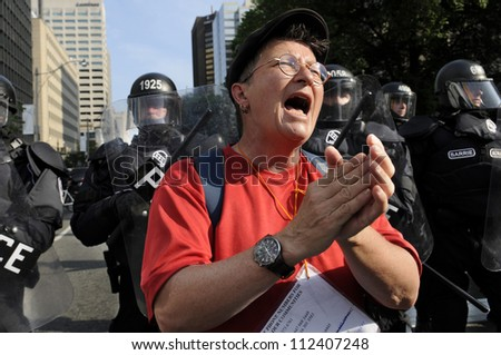 TORONTO-JUNE 25: A protester clapping and initiating her fellow protesters during the G20 Protest on June 25, 2010 in Toronto, Canada.