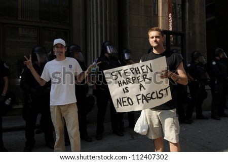 TORONTO-JUNE 25:  A protester holding a banner saying the Prime Minister of Canada is a fascist while another one makes  a funny face during the G20 Protest on June 25, 2010 in Toronto, Canada.