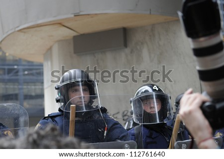 TORONTO-JUNE 26:   A  riot police officer looks at a photographer  with suspicion during the G20 Protest on June 26 2010 in Toronto, Canada. - stock photo