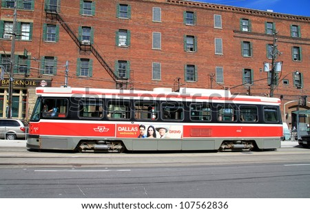 TORONTO - JUNE 29, 2012: A streetcar in a city street on June 29, 2012 in Toronto. The Toronto Transit Commission (TTC) operates 11 streetcar lines and 248 streetcars.