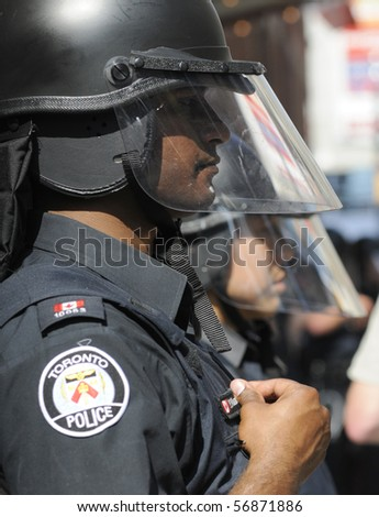 TORONTO-JUNE 25:  A Toronto Police  officer fixing his name tag during  the G20 Protest on June 25, 2010 in Toronto, Canada.