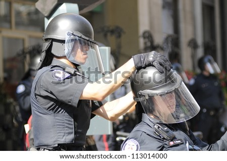 TORONTO-JUNE 25:   A Toronto police officer helps his fellow female colleague to fix her helmet during the G20 Protest on June 25, 2010 in Toronto, Canada.