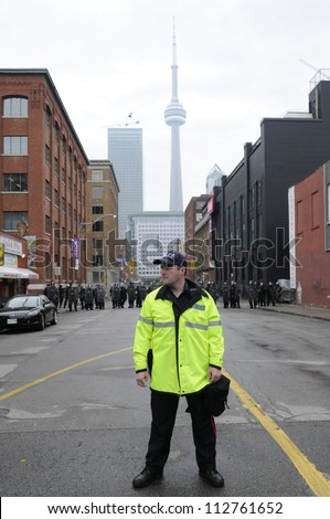 TORONTO-JUNE 26:  A Toronto police officer standing in front of a perimeter formed by the riot police  during the G20 Protest on June 26 2010 in Toronto, Canada.