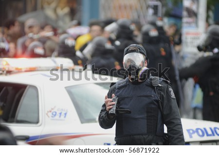 TORONTO-JUNE 26:  A Toronto Riot Police officer with his gas mask on, photographing the protesters  during the G20 Protest on June 26, 2010 in Toronto, Canada.