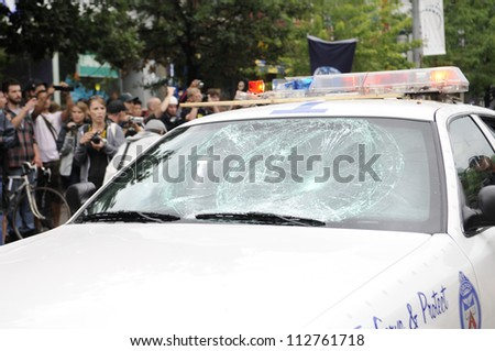 TORONTO-JUNE 26:   A vandalized police car lies on the street while citizens takes pictures  during the G20 Protest on June 26 2010 in Toronto, Canada.