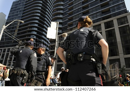 TORONTO-JUNE 25: A  woman police officer keeping a close eye on the proceedings during the G20 Protest on June 25, 2010 in Toronto, Canada.