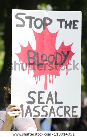 TORONTO-JUNE 25: An animal activist with a sign- protesting against the decision of the Canadian Government  to allow people to hunt seals during the G20 Protest on June 25, 2010 in Toronto, Canada.