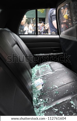 TORONTO-JUNE 26:   Broken glasses lie of the back seat of a police car that was vandalized by the protesters during the G20 Protest on June 26 2010 in Toronto, Canada. - stock photo