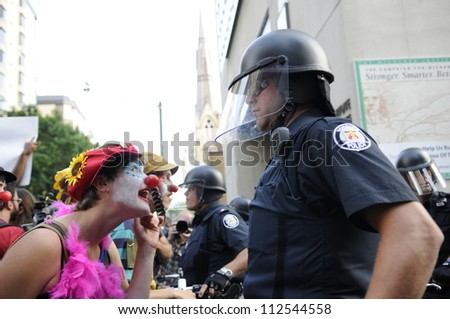TORONTO-JUNE 25:   Clown dressed activists teasing the police officers during the G20 Protest on June 25  2010 in Toronto, Canada.