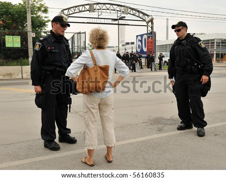 TORONTO-JUNE 27: Parent of young detained protester pleads with police in front of Toronto Film Studios at G20 protest on June 27, 2010 in Toronto.