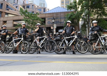 TORONTO-JUNE 28:   Police officers forming a cycle barricade in front of the police headquarters during the G20 Protest on June 28, 2010 in Toronto, Canada.