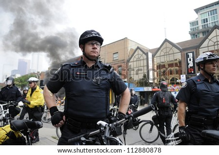 TORONTO-JUNE 26:   Police officers protecting the crime scene after a police patrol car was torched by the vandals during the G20 Protest on June 26, 2010 in Toronto, Canada.