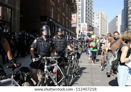 TORONTO-JUNE 25: Police on by-cycles keeping an eye on the protesters during the G20 Protest on June 25, 2010 in Toronto, Canada.