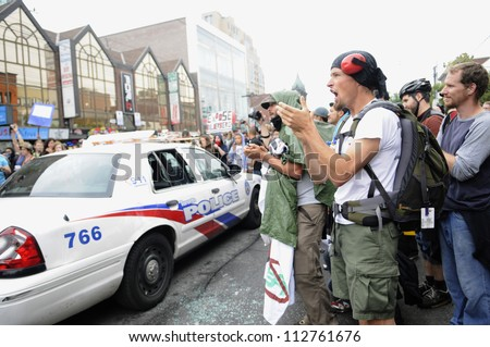 TORONTO-JUNE 26:   Protesters chanting slogans and singing songs in front of a Toronto police vehicle during the G20 Protest on June 26 2010 in Toronto, Canada. - stock photo
