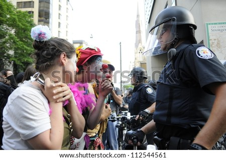 TORONTO-JUNE 25:  Protesters dressed as clowns making fun of the police officers  during the G20 Protest on June 25  2010 in Toronto, Canada. - stock photo