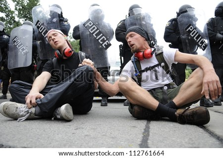 TORONTO-JUNE 26:   Protesters singing  while being sitted in front of the riot police during the G20 Protest on June 26 2010 in Toronto, Canada. - stock photo