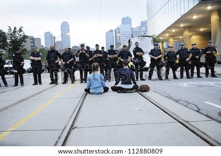 TORONTO-JUNE 26:  Protesters sitting on the streets while the police officers keep a close eye on them during the G20 Protest on June 26, 2010 in Toronto, Canada.