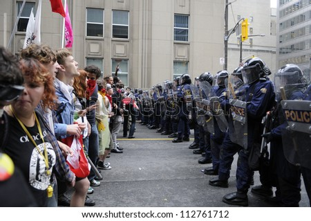 TORONTO-JUNE 26:  Protesters stand face to face with the riot police officers  during the G20 Protest on June 26 2010 in Toronto, Canada.