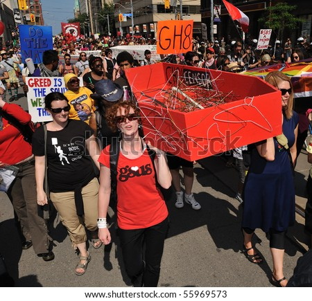 TORONTO-JUNE 25: Protesters walk with model of red coffin at G20 Protest on June 25, 2010 in Toronto, Canada.