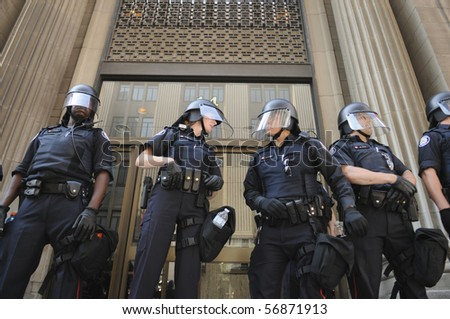 TORONTO-JUNE 25:  Toronto Police officers in riot gear guarding the entrance of a  financial building during the G20 Protest on June 25, 2010 in Toronto, Canada.