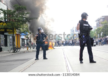 TORONTO-JUNE 26:   Toronto police officers surrounding a torched police car while the people watches on during the G20 Protest on June 26, 2010 in Toronto, Canada.
