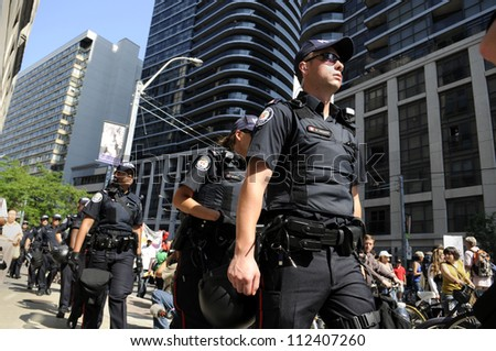 TORONTO-JUNE 25: Toronto police  walking on the sidewalks as the rally take control of the streets during the G20 Protest on June 25, 2010 in Toronto, Canada.