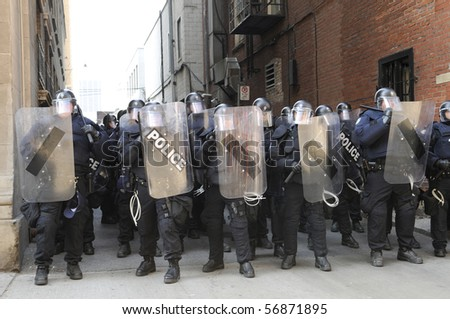 TORONTO-JUNE 25:  Toronto Riot Police restricting protesters from entering an alley between two financial buildings during the G20 Protest on June 25, 2010 in Toronto, Canada.