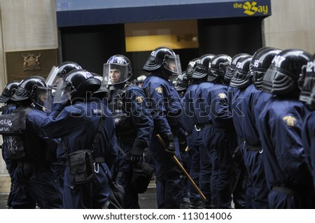 TORONTO-JUNE 26: Two group of  police officers facing their back to each other to keep eye on a critical intersection in Downtown Toronto during the G20 Protest on June 26, 2010 in Toronto, Canada. - stock photo