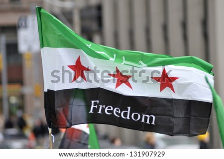TORONTO-MARCH 16 A protester waiving a Syrian flag during a protest rally organized to raise awareness and commemorate two years of Syrian revolution on March 16 2013 in Toronto Canada