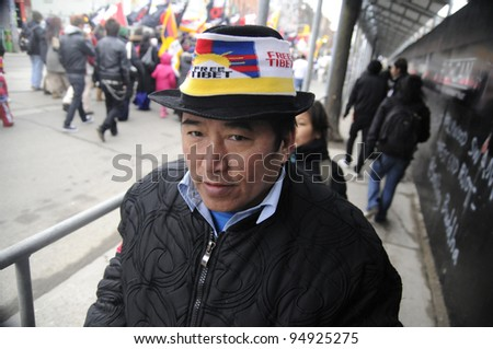 TORONTO - MARCH 10:  A Tibetan man -wearing a Tibetan flag cap participating in a rally organized to protest against the Chinese occupation of Tibet on March 10 2009 in Toronto, Canada.