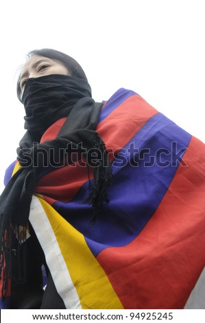 TORONTO - MARCH 10:  A Tibetan woman wrapped in a Tibetan flag marching in a rally organized to protest against the Chinese occupation of Tibet on March 10 2009 in Toronto, Canada.