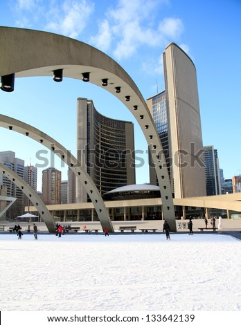 TORONTO - MARCH 16: Skating on Nathan Phillips Square outdoor rink in Toronto on March 16, 2013. In Winter, the City Hall pool is frozen into a popular outdoor skating rink.