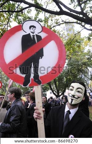 TORONTO - OCTOBER 15: A demonstrator holding a sign to denounce corporate money laundering during the Occupy Toronto Movement on October 15, 2011 in Toronto, Canada.