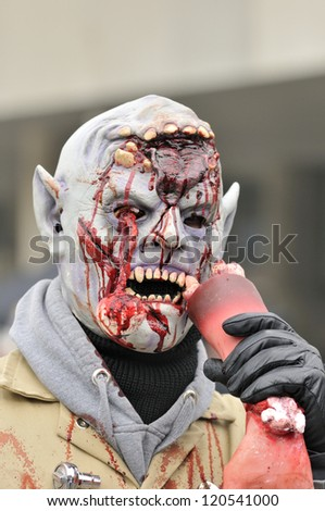 TORONTO-OCTOBER 20:A participant with fake blood and teeth trying to bite fake human hand during the Halloween parade on October 20, 2012 in Toronto, Canada.