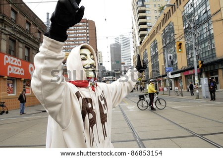 TORONTO - OCTOBER 17: A protestor wearing a guy fawkes mask walking in a rally  during the Occupy Toronto Movement on October 17, 2011 in Toronto, Canada.