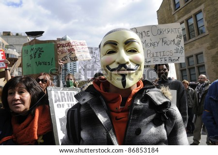 TORONTO - OCTOBER 17: A protestor wearing  guy fawkes mask walking in a rally  during the Occupy Toronto Movement on October 17, 2011 in Toronto, Canada.