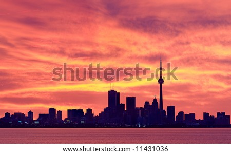 Toronto's downtown core set against glowing orange sky moments before sunrise