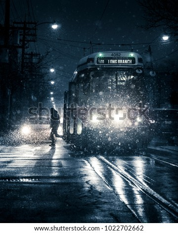 TORONTO STREETCAR AT NIGHT - Winter snow storm with man getting off public transit train/vehicle. Silhouetted figure in downtown, urban, city street during heavy snowfall. Toronto, Ontario, Canada