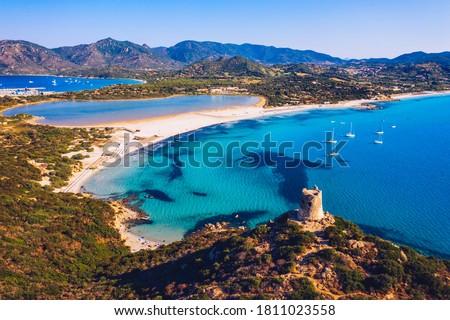 Torre di Porto Giunco Tower and Simius Beach near Villasimius, Sardinia, Italy. View from flying drone. Torre di Porto Giunco tower on Carbonara cape. Aerial morning view of Sardinia island, Italy