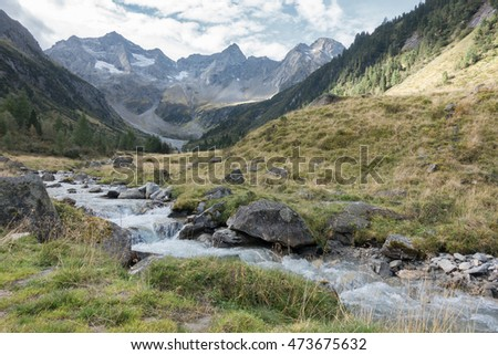 Torrent from the glaciers in the Alps #473675632