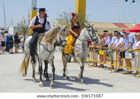 TORREVIEJA, SPAIN,  - MAY 13: Riders in custom Spanish dress taking a walk  in the square of the fair on the  May fair the day May 13, 2012 in Torrevieja, Spain
