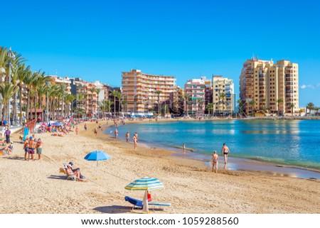 TORREVIEJA, SPAIN - NOVEMBER 13, 2017: People enjoying and sunbathing at the Playa De Los Locos beach.